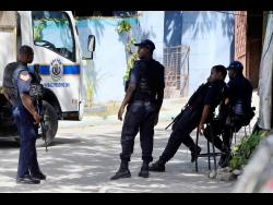 Police at the scene of a shooting in August Town, St Andrew, yesterday.