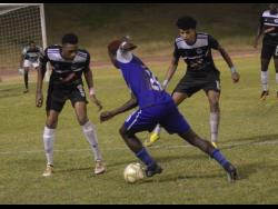 Reno's Fancy-Hue Stewart (centre) drives forward while being closely marked by Cavalier's Jamoi Topey (left) and his teammate Leonardo Rankine during their Red Stripe Premier League game at the Stadium East playing field last season.