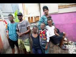 Ricardo Makyn/Chief Photo Editor Leecroft Dunnigan and his common-law wife, Jaqueline Shirley, pose with their children at their home on Wildman street, downtown Kingston.