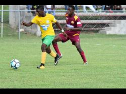 Jay Jamieson (left) of Petersfield High School attempting to dribble away from Port Antonio High School's Errol Lane in their semi-final encounter of the ISSA/WATA Ben Francis Knockout Cup at the Juici Patties Park on Thursday, November 15, 2018.