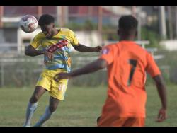 Waterhouse player Kenroy Howell (left)  heads the ball away while Tivoli's Junior McGregor looks on in their Red Stripe Premier League encounter at the Edward Seaga Complex on Thursday, December 19, 2019.