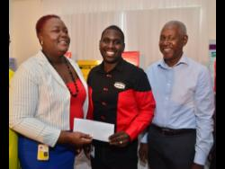 Promotions manager at Grace Kennedy, Ricardo Smith (centre), presents a sponsorship cheque to meet chairman Camille Allen during the launch of the 2020 Camperdown Classic at the Spanish Court hotel  yesterday. Looking on is Peter Hibbert, the former Camperdown High sprinter, who will be this year's honouree.