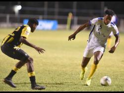 Waterhouse's Stephen Williams (right) dribbles away from Peterson Pierre (left) of Don Bosco from during their Concacaf Caribbean Club Championships match at the Anthony Spaulding Sport Complex, yesterday.