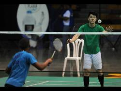 Anthony Murillo of Panama (blue) and  Matthew Lee of Jamaica  take part in a rally at the Jamaica International 2017 badminton tournament at the Indoor Sporting Centre on February 3, 2017.