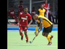 Jamaica's Nicholas Beach dribbles by  Panama's  Angelo Boodie in the Central American and Caribbean Games qualifier at the Mona hockey field on November 5, 2017.