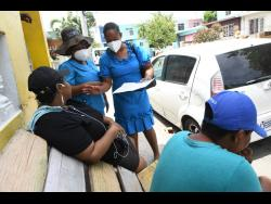 Health workers speak with residents of Tivoli yesterday.