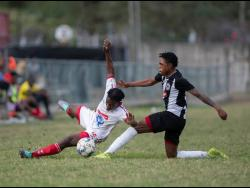 Ronaldo Webster of Cavalier FC tackles UWI FC's Nacquain Brown (left) in their Red Stripe Premier League Fixture played at the UWI Mona Bowl on Sunday February 23.