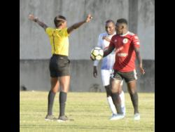 Referee Cardella Samuels (left) stands her ground over a decision to rule out a goal scored by Mount Pleasant FA's Cardel Benbow during a Red Stripe Premier League match against hosts Portmore United at the Spanish Town Prison Oval last year January.