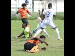 Lynval Wilson (right) from Reno FC blocks a ball heading towards goal from Ramaine Brakenridge (left) from Tivoli Gardens FC after Dennis Taylor  (second left) was left beaten on the ground in a 2018 Premier League match.  Also on the ground is Tivoli's Andre Moulton.