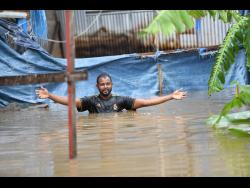 During recent flood rains, Dwayne McKoy, a resident of Grants Crescent in Hampton Green, Spanish Town, wades through chest-high floodwaters to the rear of his home, from which he operates a furniture workshop. McKoy said that flooding has been a long-standing issue in the Spanish Town community.