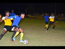 File Tevoy Colespring (second left) of Meadforest FC holds off Barbican FC's Damian English during their Magnum KSAFA Super League first-round clash at Constant Spring Complex in 2018.