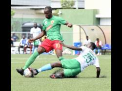 Vere United's Shamar O'Connor (right) makes a slide tackle against Levaughn Williams of Humble Lion during their Jamaica Premier League match on Sunday. Vere United won 3-1.