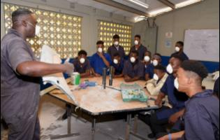 Auto body repair instructor Fitzgerald Thompson (left) conducts a class.