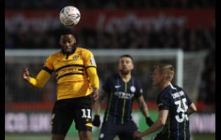 AP Newport County's Jamille Matt (left) heads the ball past Manchester City's Oleksandr Zinchenko during their English FA Cup fifth round match at Rodney Parade stadium in Newport, Wales, on Saturday, February 16.