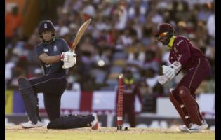 ap photos England's Joe Root sweeps a shot against the Windies during the first one-day international cricket match at the Kensington Oval in Bridgetown, Barbados, yesterday.