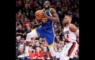 Golden State Warriors forward Draymond Green (left) prepares to shoot over Portland Trail Blazers guard Damian Lillard during the first half of Game 3 of the NBA basketball play-offs Western Conference finals on Saturday.