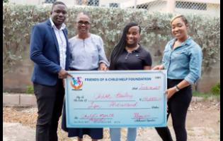 Founder of Help A Child Foundation, Jason Evans (left), presents a cheque to Chloe Bailey (second right), a recipient of the foundation's outreach activities, while her grandmother Ida Hughes (second left), and Petagaye Ferguson, the foundation's legal adviser, look on.