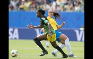 Reggae Girlz team captain Konya Plummer (left) dribbles by Brazil's Beatriz Zaneratto Joao in the Jamaica's opening game of the 2019 FIFA Women's World Cup against Brazil on June 9, 2019.