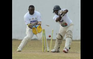 Kenroy Henriques (right) from Yallahs is bowled by Ryan Brown (out of picture), while wicketkeeper Domain Taylor looks on during the Social Development Corporation (SDC) T20 Community Cricket held at the Goodyear Oval in Springfield, St. Thomas, on Sunday, May 26, 2019.