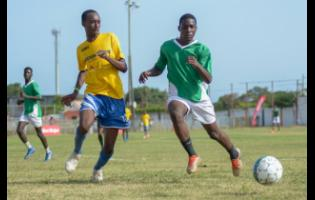 Blain Byam of Santos  (left) challenges Romario Campbell of Tivoli Gardens for a loose ball in the Under-17 match yesterday.