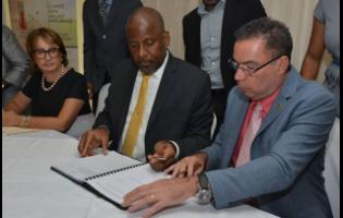 Daryl Vaz (right), minister without portfolio, in the Ministry of Economic Growth and Job Creation, signs the contract with Enterprise Electronics Corporation for the installation of a new Weather Radar System for Jamaica, with Dr Wayne Henry, director general of the Planning Institute Of Jamaica.