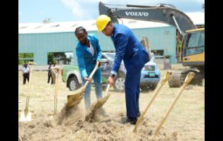 Prime Minister Andrew Holness (right) and St Thomas-born dancehall artiste Popcaan, given name Andrae Hugh Sutherland, break ground for the Morant Bay Urban Centre yesterday, on the grounds of the old Goodyear Factory yesterday.