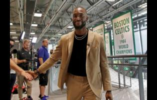 Newly acquired Boston Celtics guard Kemba Walker shakes a hand as he leaves an interview at the Celtics' basketball practice facility, in Boston, Massachusetts, yesterday.