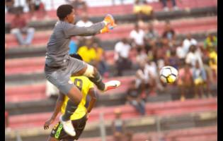 Dominica goalkeeper Elie Tafari (front) clears the ball, ahead of the approaching Tevin Shaw (not pictured) of Jamaica.