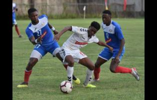 Trey Bennett (centre) from UWI FC tries to go between the Portmore United pair of Sheldon McKoy (left) and Venton Evans (right) during their Red Stripe Premier League football match  at the Spanish Town Prison Oval yesterday.