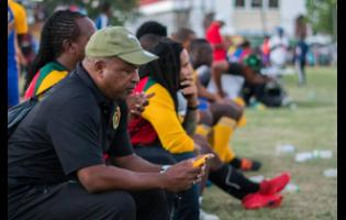 Lenny Hyde (left) sits on the bench of Falmouth United, along with owner Ky-mani Marley, during a Western Confederation match against Montego Bay United on December 8, 2019.