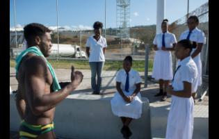 Olympian Yona Knight-Wisdom (left) shares diving advice with members of the Immaculate Conception High School swim team and Kaizen Swim Club members in between dives in a training session at the National Aquatic Centre in Kingston last Thursday January.