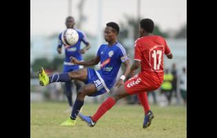 Mount Pleasant's Kemar Beckford (left) brings the ball under control while being watched by UWI defender Stephen Barnett during a Red Stripe Premier League match last season. Beckford is the leading scorer in this year's competition.