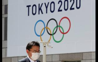 In this Wednesday, March 25, 2020, file photo, a masked man walks in front of a Tokyo Olympics logo at the Tokyo metropolitan government headquarters building in Tokyo. The Tokyo Olympics have been moved to next year. But countless questions remain. They revolve around 11,000 Olympic athletes and 4,400 Paralympic athletes. They also include 206 national Olympic committees, sports federations, thousands of contracts, and billions of dollars.