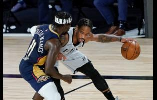 San Antonio Spurs forward DeMar DeRozan (right) tries to keep the ball away from New Orleans Pelicans guard Jrue Holiday (11) during the second half of an NBA basketball game, Sunday, August 9, 2020.