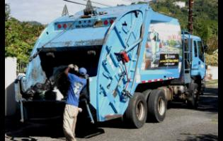 A member of the work crew puts domestic waste in the back of a National Solid Waste Management Authority compactor truck.