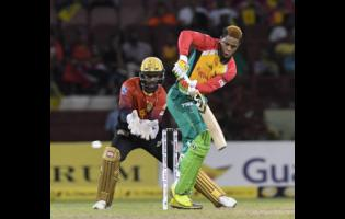 Shimron Hetmyer of Guyana Amazon Warriors hits a 4 as Denesh Ramdin of Trinbago Knight Riders watches during the Hero Caribbean Premier League play-off match 31 between Guyana Amazon Warriors and Trinbago Knight Riders at Guyana National Stadium on September 11, 2018.