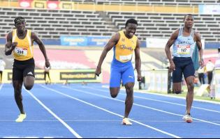 Bryan Levell (right) picks up points for Edwin Allen High School in the Class One Boys 100m final.  Sachin Dennis (centre) of St Elizabeth Technical High School took the gold medal, while Antonio Watson of Petersfield High School took silver.