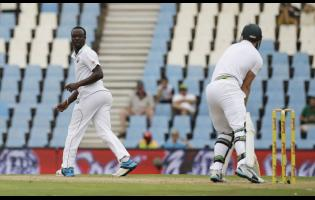 West Indies' bowler Kemar Roach (left) looks on after an unsuccessful appealing for LBW against South Africa's batsman AB de Villiers during a Test match at Centurion Park in Pretoria, South Africa on Wednesday, December 17, 2014.