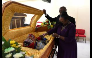 Culture Minister Olivia Grange places a rose on the body of Lee 'Scratch' Perry at Perry's Funeral Home yesterday in St Catherine. Looking on is Peter Perry, CEO of the funeral home. The body was later transported to Hanover for burial.
