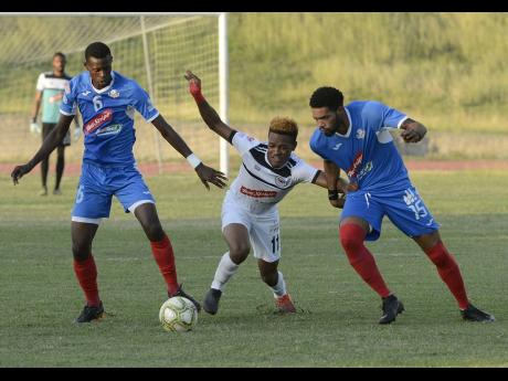 file Cavalier FC's Alex Marshall (centre) weaves his way between Portmore United's Chavany Willis (left) and Cleon Pryce during their Red Stripe Premier League game at Stadium East on Sunday, December 23, 2018.