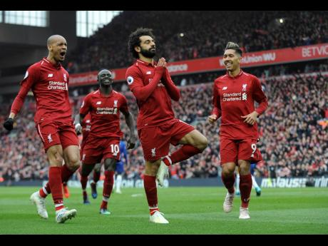 Liverpool's Mohamed Salah (centre) celebrates with teammates after scoring his side's second goal during the English Premier League match between Liverpool and Chelsea at Anfield Stadium in Liverpool, yesterday.