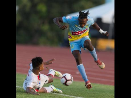 Wendy St Felix (left) of Real Hope FA slide tackles Ricardo Thomas of Waterhouse FC, putting the ball into touch in their FLOW Concacaf Caribbean Club Championhsip match at Stadium East yesterday afternoon.