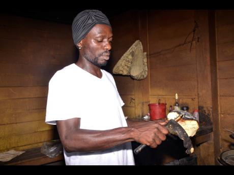 Michael peels roasted breadfruit in anticipation of getting a sale.