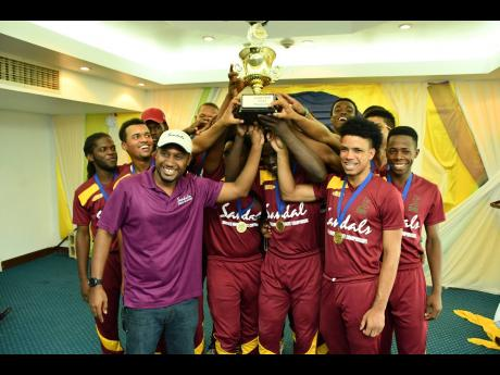 Sandals Resorts Public Relations Manager – Sponsorships Crissano Dalley (front left) raises the Sandals Under-19 Cricket Championships Trophy with the Southern Sparks.