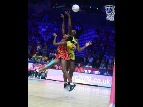 Jamaica's Jhaniele Fowler (right) challenges Lilian Ajio of Uganda for the ball.