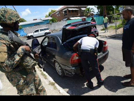 Members of the Jamaica Defence Force and the Jamaica Constabulary Force doing spot checks in the Corporate Area.