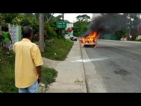 The businessman staring in shock as his Toyota Liteace is engulfed in flames.