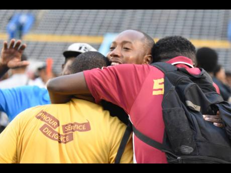 St Andrew Technical High School head coach Philip Williams (centre) embraces members of his technical staff after the penalty shoot-out in their ISSA/Digicel Manning Cup semi-final match against Wolmer's Boys School at the National Stadium, in St Andrew, yesterday.