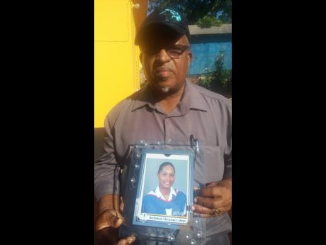 Neville Sinclair holds a photo of his daughter Nevia, who was murdered Sunday night in her room. at the family home.