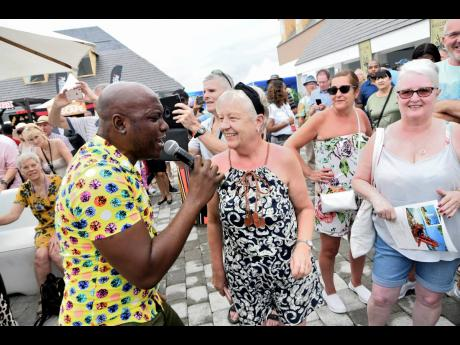 A member of the Ashe company performs for the tourists at the arrival of the Marella Discovery 2 at the Port Royal cruise ship pier yesterday.